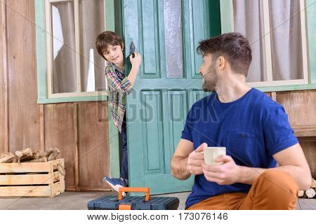 man sitting on porch with tea cup and looking at boy behind