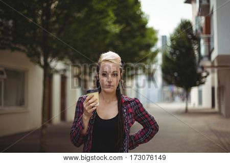 Woman standing with coffee cup on street