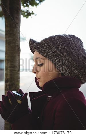 Woman holding a cup of coffee in street