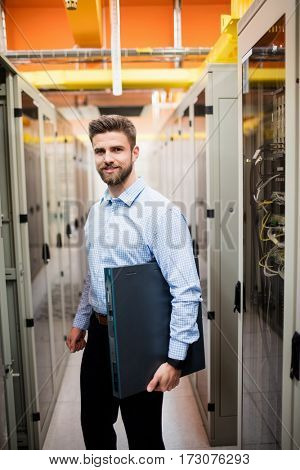 Portrait of technician holding a server in server room