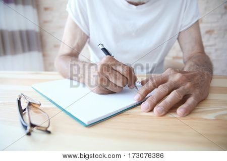 Male hands writing in copybook, closeup