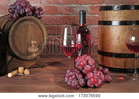 Glasses of red wine, grapes and wooden barrels on table