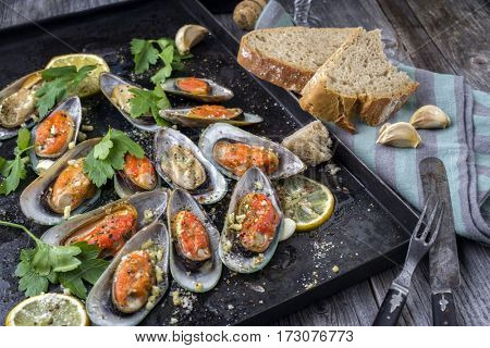 Backed Green Shell Mussels on old rustic sheet with Bread