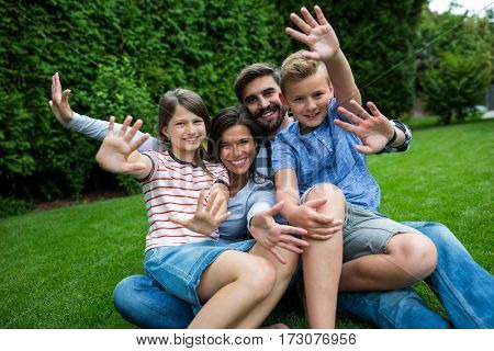 Portrait of happy family sitting on grass in park on a sunny day
