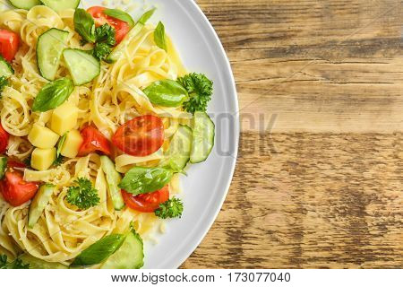 Pasta salad with tomatoes and cucumber on wooden background