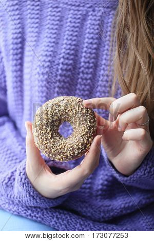 Donut with chocolate and nuts in the hands of a girl close-up. Only hands on background svitora. Photo without a face.
