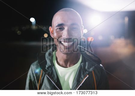Portrait of urban female runner standing under bridge at night. Beautiful young woman standing on the street.