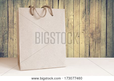 Isolated recycled paper shopping bag. Wooden background. Empty copy space for Editor's content.