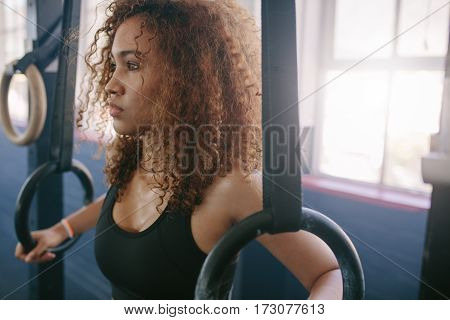 Close up shot of young fit woman doing pull-ups on gymnastic rings. African female exercising with rings at gym.