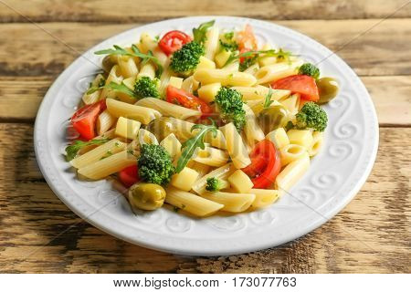 Pasta salad with tomatoes and olive on wooden background