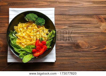 Pasta with ingredients in plate on wooden table