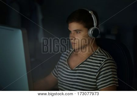 Teenager playing computer game at home late in evening