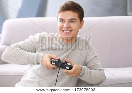 Teenager playing videogame at home