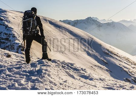 Mountaineer With Ice Axes And Backpack In The Winter Mountains Admiring The Views