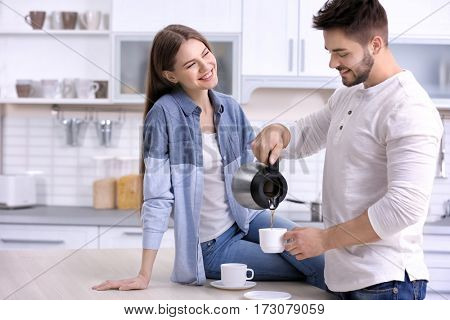 Cute young couple drinking coffee in kitchen