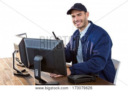 Happy Security officer talking on walkie-talkie while using computer against white background
