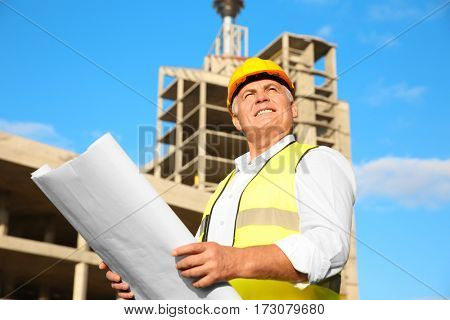 Senior engineer with drawing standing against unfinished building
