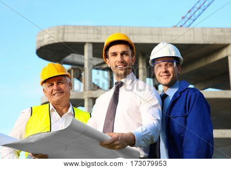 Engineer with drawing and workers standing against unfinished building