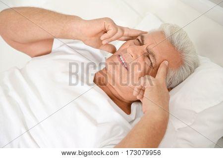 Senior gentleman suffering from pain in bedroom