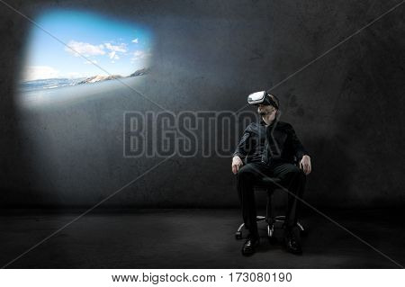 Businessman Rests On Chair In Some Hangar With Virtual Reality Headset With Beautiful Landscape Proj