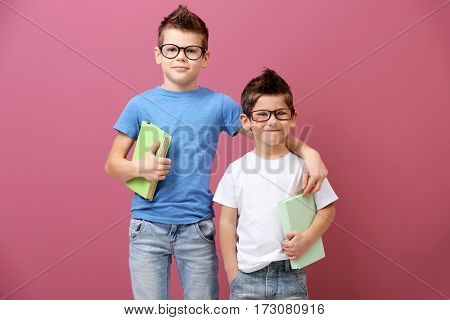 Cute little brothers with books on pink background