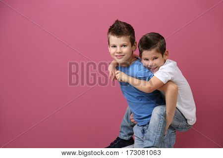 Cute little brothers standing on pink background