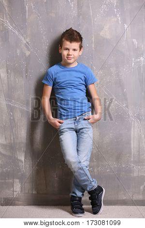 Cute little boy on grey textured background
