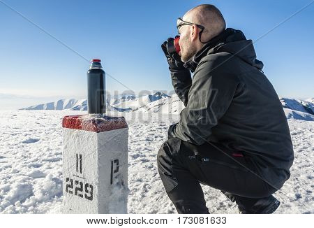 Tourists Drink Hot Tea In The Winter In The Mountains.