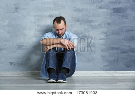 Handsome depressed man sitting on floor near wall