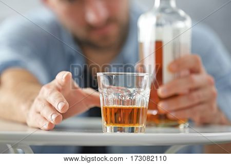 Male hand with glass of whisky, closeup