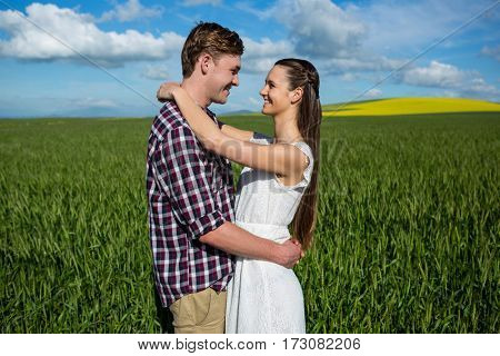 Romantic couple embracing each other in field on a sunny day