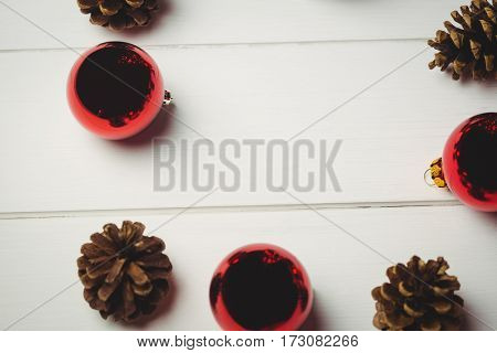 Close-up of red christmas bauble and pine cone on wooden table