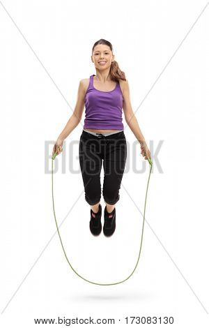 Full length portrait of a female athlete exercising with a skipping rope isolated on white background