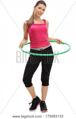 Full length portrait of a female athlete exercising with a hula-hoop isolated on white background