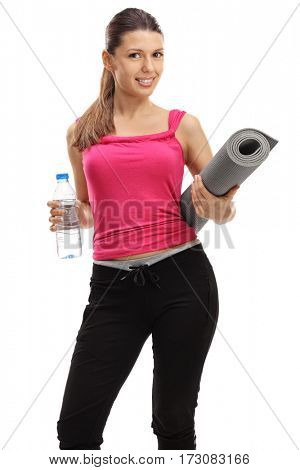 Girl holding a bottle of water and an exercising mat isolated on white background