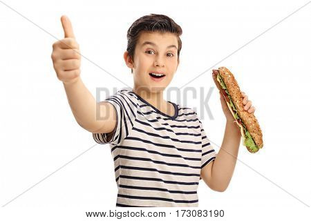 Joyful young boy holding a sandwich and giving a thumb up isolated on white background