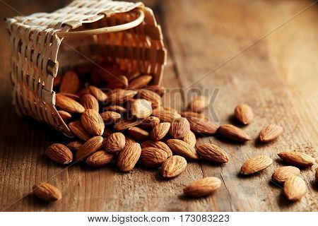 Whole almonds falling out of a small basket. A pile of almonds on a wooden surface.