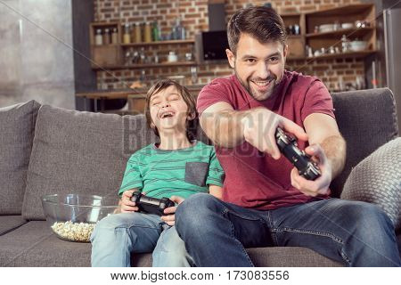 cheerful father and son playing video game at home