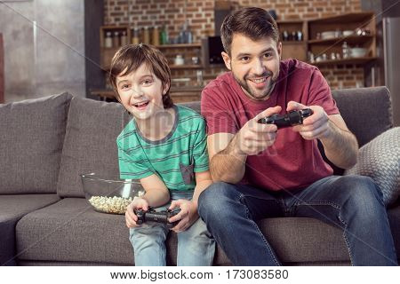 smiling father and son playing video game at home