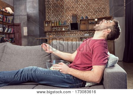 man eating popcorn while watching movie at home