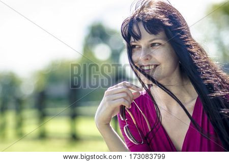 Beautiful slender brunette girl with freckles in a red dress in a summer park