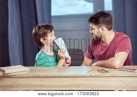 son showing done homework to father at home