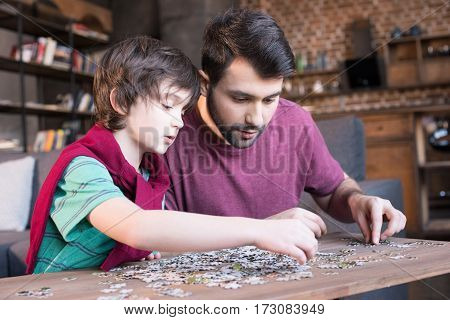 side view of focused father and son playing with puzzles at home