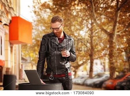 Handsome young man with laptop outdoors