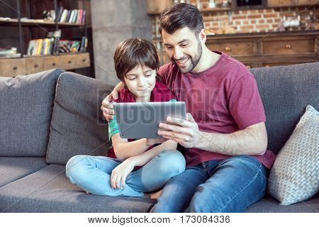 smiling father and son using digital tablet at home