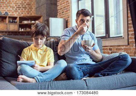 man having breakfast while son doing homework near by