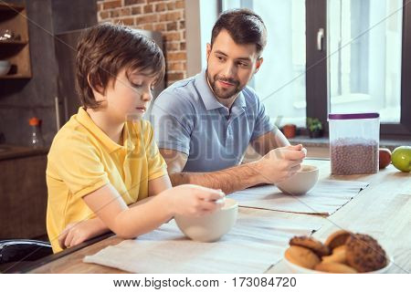 Father and son sitting at kitchen table and having chocolate balls for breakfast
