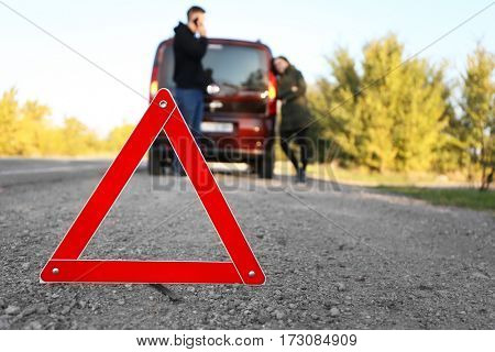 Red warning triangle on asphalt road. Couple near broken down car