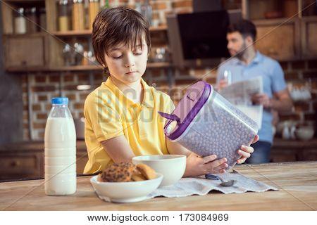 Cute little boy holding chocolate balls for breakfast