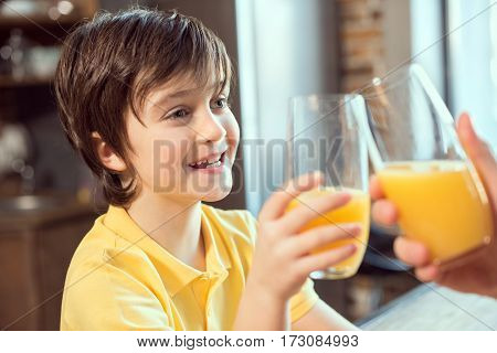 Smiling little boy and father clinking glasses with fresh juice